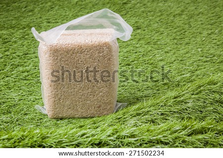 Jasmine brown rice in vacuum plastic bag package on green grass - stock photo