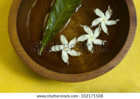 Jasmine flowers in water in a wooden bowl on yellow hand-made paper - stock photo