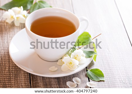 Jasmine green tea in a cup with jasmine flowers