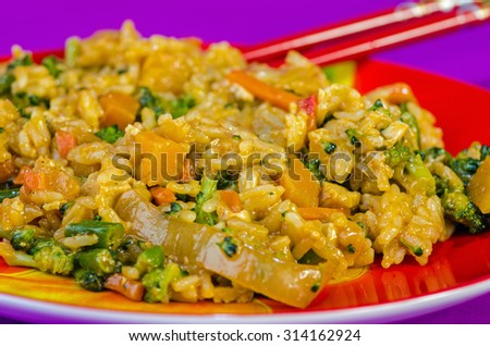 Jasmine rice and vegetables in Thai Red Curry on bright red plate against purple background.  Bright colors of typical Oriental Restaurant. Selective focus with shallow dof. - stock photo