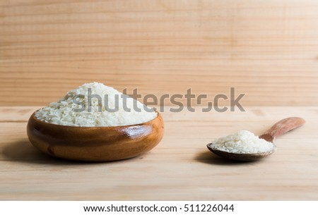 Jasmine rice in a wooden bowl on wooden background