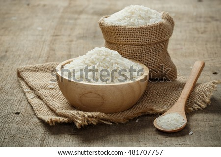 Jasmine Rice in bowl and burlap sack on wooden table