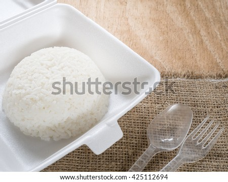 Jasmine rice in foam box with plastic Spoon and fork. - stock photo