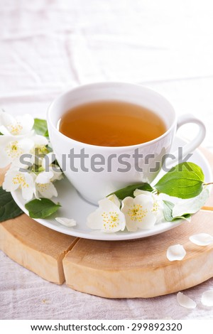 Jasmine tea in a cup with fresh jasmine flowers