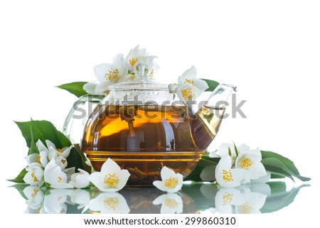 jasmine tea in a teapot with a branch of jasmine on  white background - stock photo