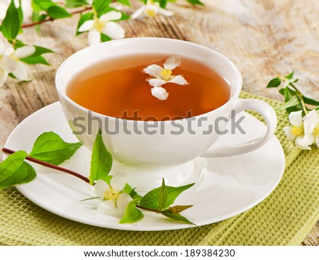 Jasmine tea in a white cup with flowers . Selective focus