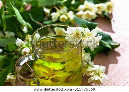 jasmine tea in glass cup on wooden table