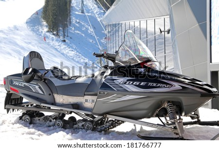 JASNA, SLOVAKIA - MARCH 13: Snowmobile in front of modern cableway FUNITEL in ski resort Jasna - Low Tatras mountains on March 13, 2014 in Jasna