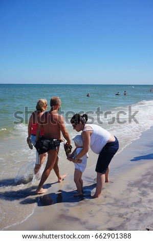 JASTARNIA, POLAND - JUNE 19, 2017: Woman and child standing next to a walking couple on a beach