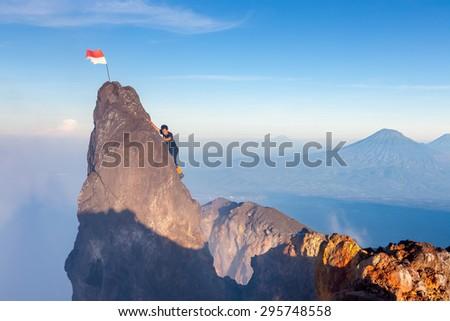 Java/Indonesia - Apr 8, 2015: Indonesian climber climbing to highest peak of Merapi volcano at Java island, Indonesia - stock photo