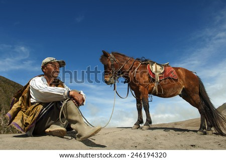 JAVA,INDONESIA-Apri l 9 :Indonesia man with the horse for tourist rent at Mount Bromo on April 9,2014 in Java , Indonesia.Mt. Bromo is an active volcano and part of the Tengger massif, in East Java. - stock photo