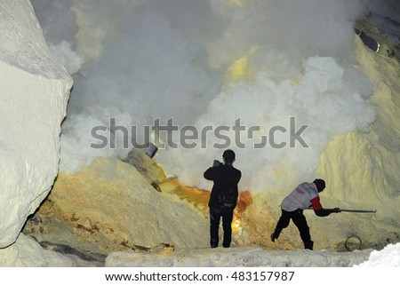 JAVA, INDONESIA - AUGUST, 9, 2016 - Miners are carrying sulfur from Ijen Volcano Blue flames at night, more than 100 kilos each one for a cheap salary