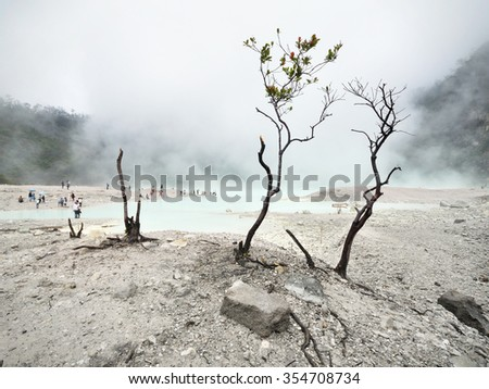 JAVA, INDONESIA - November 16, 2008: Tourists gather at the popular tourism attraction of 'Kawah Putih' volcanic crater lake on November 16, 2008 near Bandung, Java, Indonesia. - stock photo