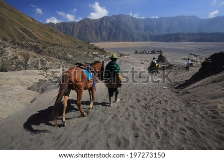 JAVA,INDONESIA-September 19:Unidentified man with the horse for tourist rent at Mt.Bromo on September 19,2012 in Indonesia.Mt. Bromo is an active volcano and part of the Tengger massif, in East Java. - stock photo