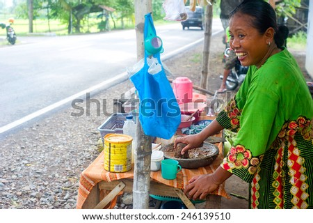 JAVA ISLAND, INDONESIA - APRIL 21,2012: A smiling woman preparing fast food near the road.With a population of 143 million, Java is the world's most populous island - stock photo