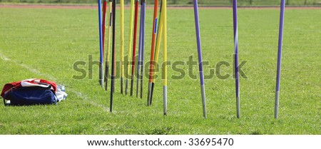 Javelins stuck in the ground and sport equipment during a training session. - stock photo
