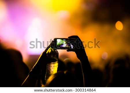 JAZ, MONTENEGRO - JULY 17 2015: Hand with a smartphone infront of the Main stage at SEA DANCE Music Festival - EXIT ADVENTURE, on July 17, 2015 at the Jaz beach near Budva, Montenegro. - stock photo