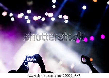 JAZ, MONTENEGRO - JULY 17 2015: Hand with a smartphone infront of the Main stage at SEA DANCE Music Festival - EXIT ADVENTURE, on July 17, 2015 at the Jaz beach near Budva, Montenegro.