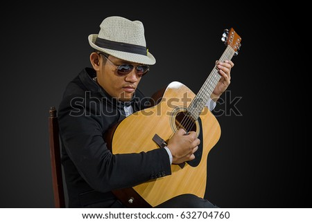 Jazz musician wearing black suit and white hat playing acoustic guitar in thailand.