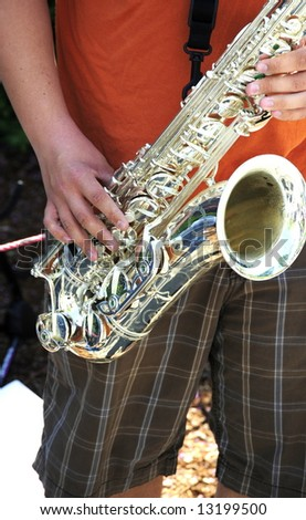 Jazz saxophone player playing a solo at a concert outdoors.