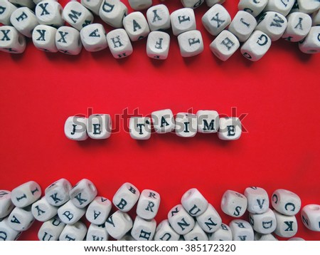 Je T'aime meaning I Love You in French written with the block letters covered over the red background