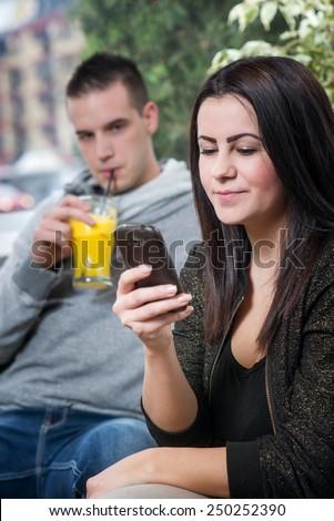 Jealous boyfriend watching his girlfriend tapping message. - stock photo