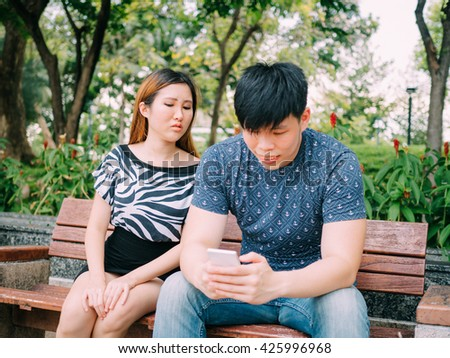 Jealous girlfriend peeking and spying her boyfriend mobile phone while he is reading a message - stock photo