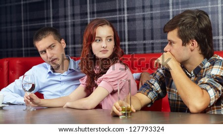 Jealous man looking at his girlfriend sitting in a restaurant - stock photo