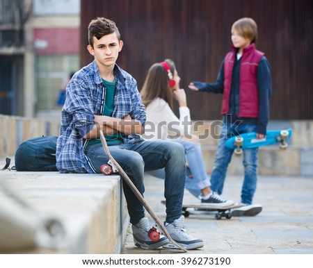 Jealous spanish teen and his friends after conflict outdoors  - stock photo