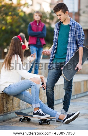 Jealous teen and his friends after conflict outdoors  - stock photo