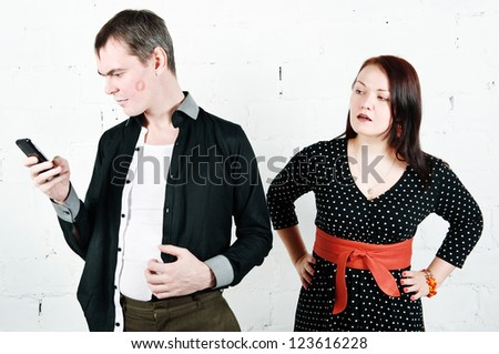 Jealous woman looking at her man chatting on telephone - stock photo