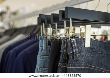 Jean pants hang on a shelf in a designer clothes store