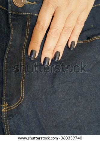 Jeans and a female fingers with blue nail polish, old photo effect