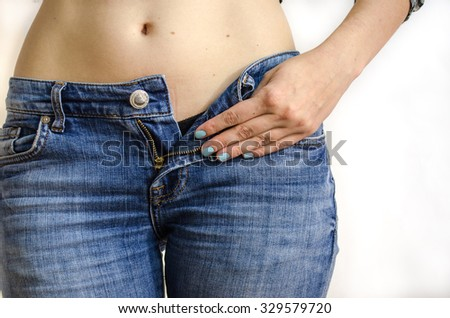 Jeans and a female hand with blue nail polish, isolated on white background. Close view