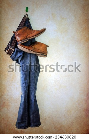 Jeans and boots hanging over grunge background - stock photo