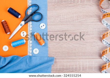 Jeans and cotton fabrics for sewing, lace, measuring tape and accessories for needlework on wooden background. Spool of thread, scissors, buttons, sewing supplies. Set for needlework top view - stock photo
