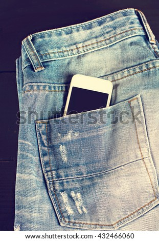 jeans and mobile phone on wooden boards. Phone in your pocket jeans - stock photo