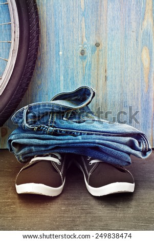 Jeans and sneakers on a background of blue wooden fence. Toning. Instagram - stock photo