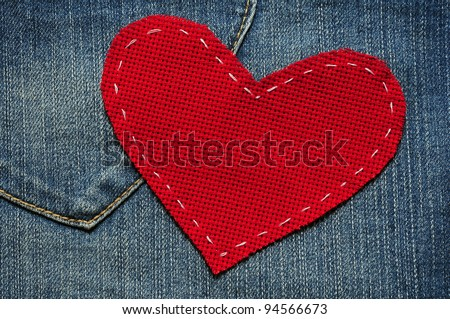 Jeans background with red heart - stock photo