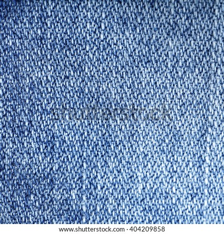 Jeans fabric background. Worn jean pants closeup of faded blue denim weave texture with vertical weave lines useful for elements of illustration, text copyspace or backgrounds. - stock photo