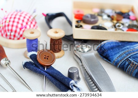 jeans Spools of threads buttons needle for sewing - stock photo