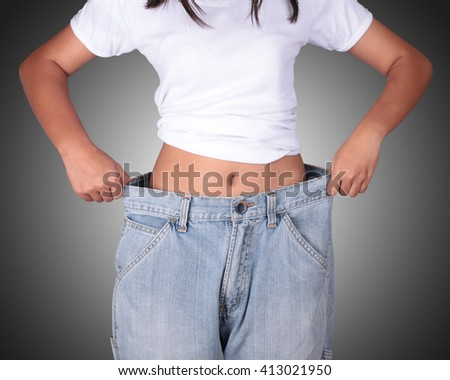 Jeans with a big old Slim girl from a good diet ago Close-up slim waist of young woman in big jeans showing successful weight loss, isolated on black background, diet concept. This has clipping path. - stock photo