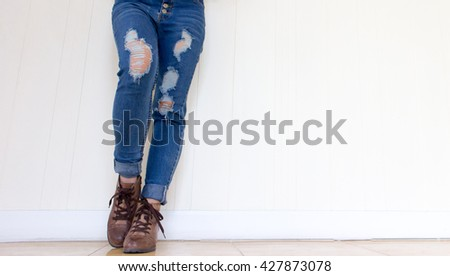 jeans Woman wearing Brown leather shoes Standing against a white wall - stock photo