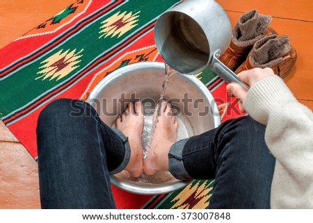 Jeansed female feet in an aluminum basin close to winter boots.
