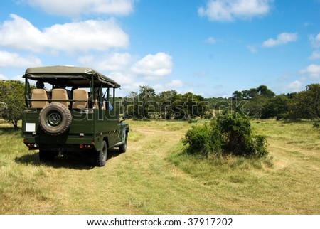 Jeep with tourist on a wild safari - stock photo