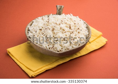 jeera rice, long-grain basmati rice flavoured with fried cumin seeds , served in a ceramic bowl, top view, isolated and front view on orange background - stock photo