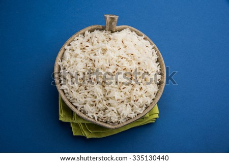 jeera rice, long-grain basmati rice flavoured with fried cumin seeds , served in a ceramic bowl, top view, isolated on blue background - stock photo