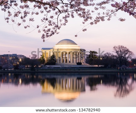 Jefferson Memorial at dawn by Tidal Basin and surrounded by pink Japanese Cherry blossoms with the monument lit by the rising sun at dawn - stock photo