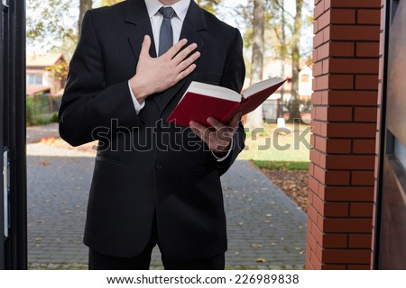 Jehovah's witness standing at the door and holding Bible - stock photo