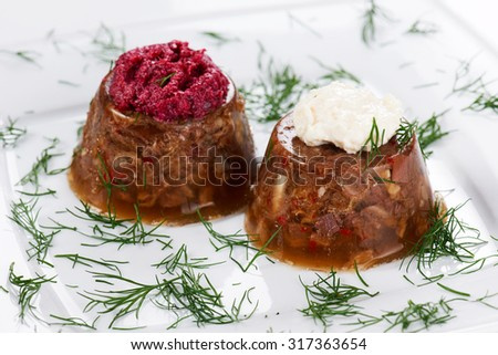 Jellied meat with red and white horseradish on a white plate.